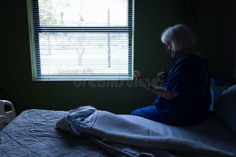 Starszy żeński cierpliwy używa telefon komórkowy przy łóżkiem szpitalnym zdjęcia stock