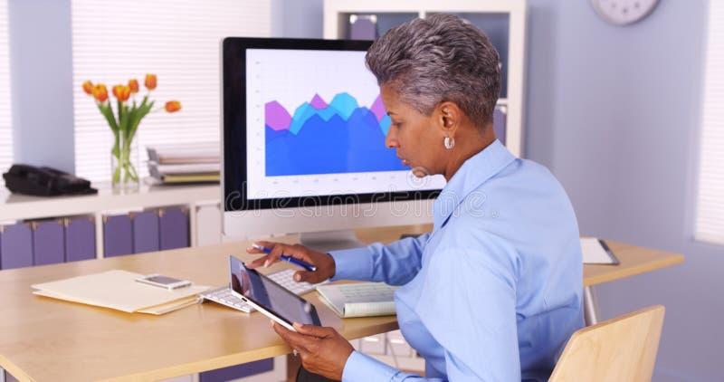 Starszy Afrykański bizneswomanu multitasking przy biurkiem obrazy stock