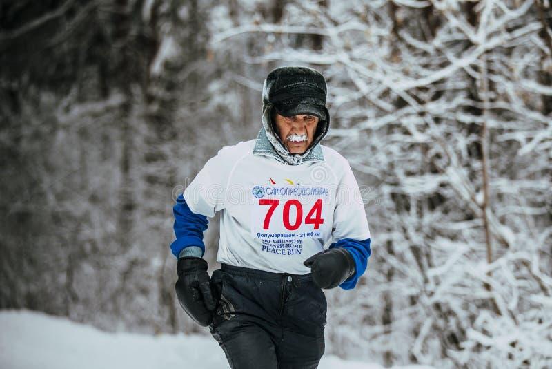 Starszy atleta biegacz biega przez śnieżnych drewien zimna pogoda oszroniejąca na jego wąsy obraz royalty free