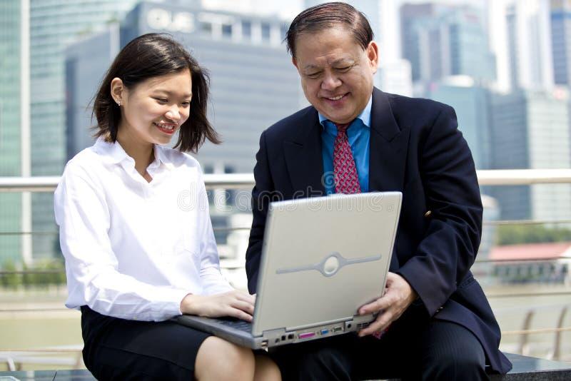 Starszy Azjatycki biznesmen i potomstwo laptopu żeński Azjatycki wykonawczy używa pecet zdjęcie royalty free