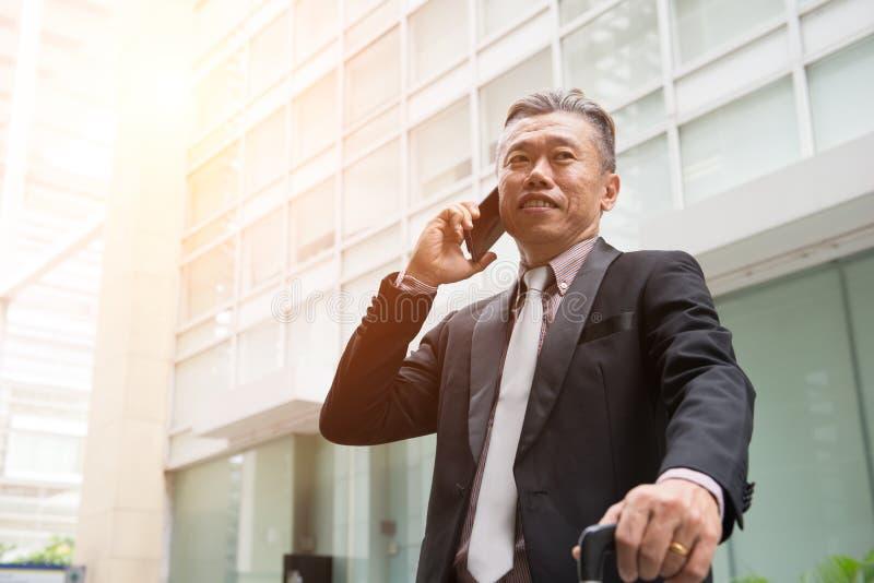 Starszy azjatykci biznesowy mężczyzna na telefonie fotografia royalty free