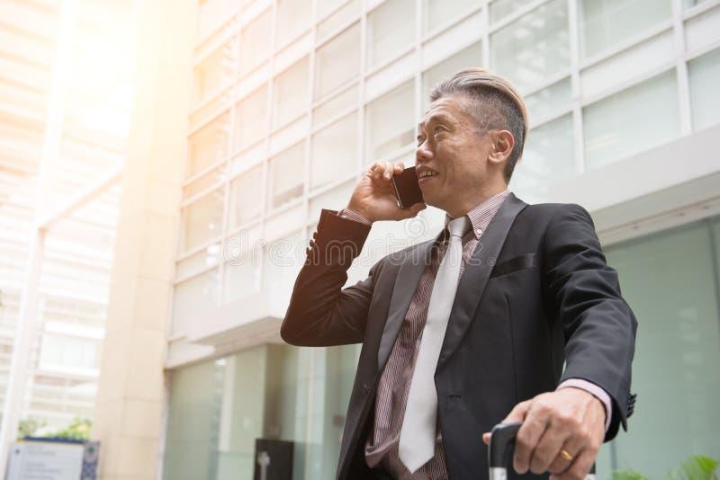 Starszy azjatykci biznesowy mężczyzna na telefonie zdjęcie stock