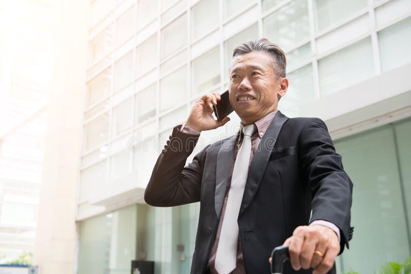 Starszy azjatykci biznesowy mężczyzna na telefonie obrazy royalty free