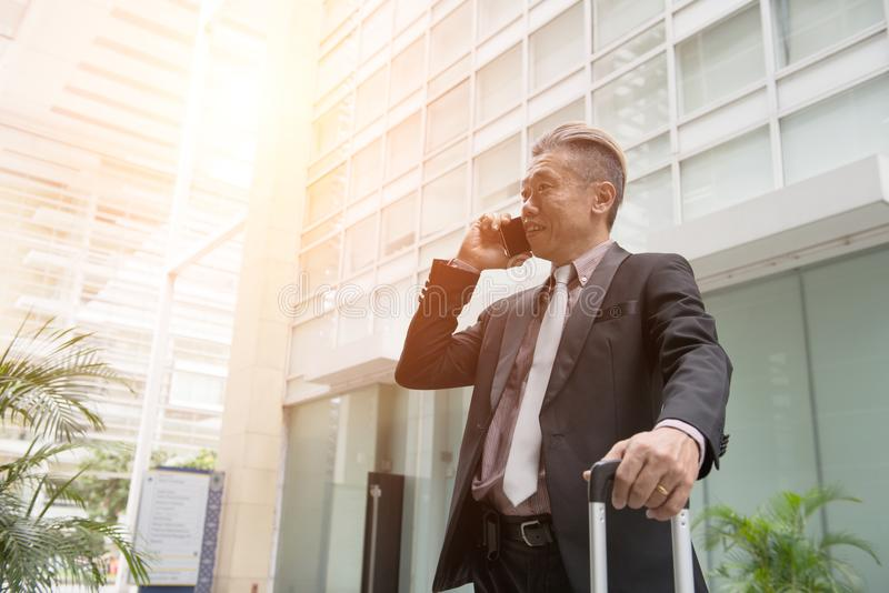 Starszy azjatykci biznesowy mężczyzna na telefonie zdjęcie royalty free