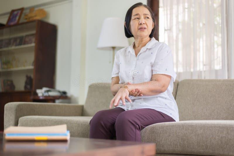Starszy azjatykci kobiety cierpienie z Parkinson choroby objawami na rękach fotografia royalty free
