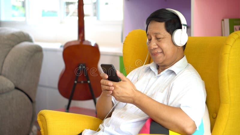 Starszy azjatykci mężczyzna używa smartphone słuchającą muzykę z hełmofonami, siedzi na kanapie w domu w żywym pokoju, Stary męsk obrazy royalty free