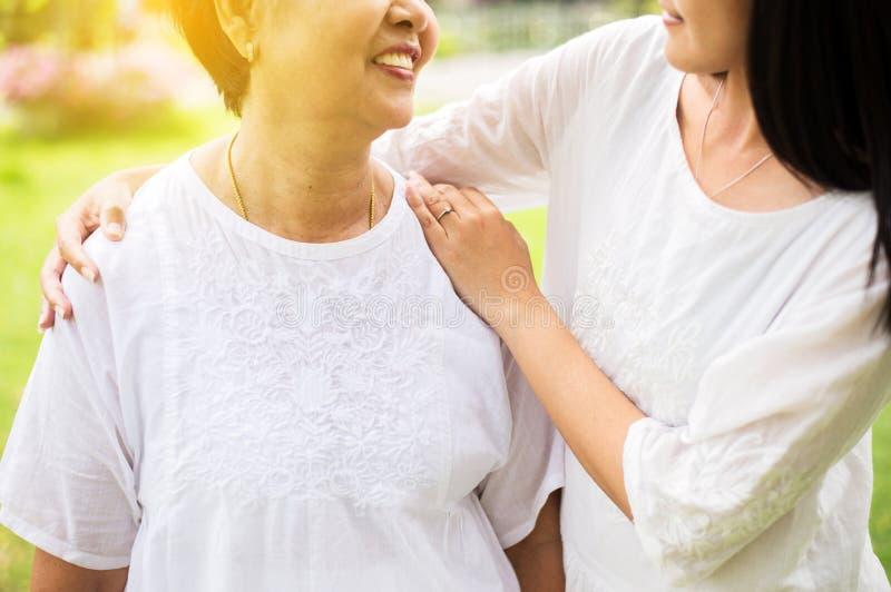 Starszy azjatykci stary macierzysty szczęśliwy z ręki córką bierze opiekę i poparcie, Zamyka w górę zdjęcia royalty free