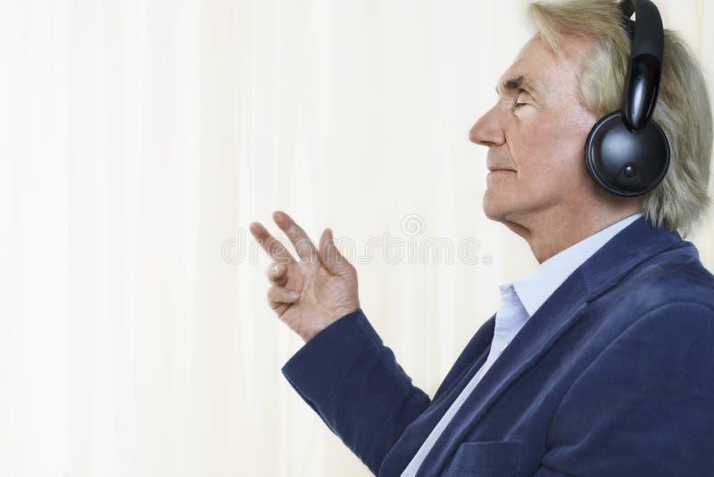 Starszy biznesmen Cieszy się muzykę Z hełmofonami zdjęcie royalty free
