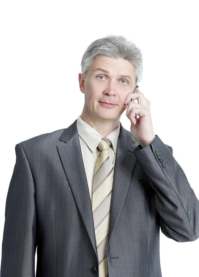 Starszy biznesmen opowiada na telefonie komórkowym odosobniony miotła biel fotografia stock