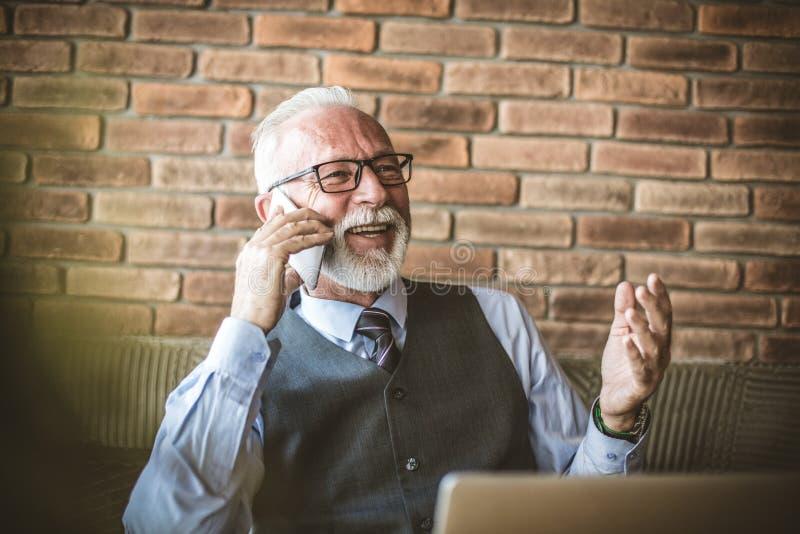Starszy biznesmen opowiada telefon szczęśliwy uśmiech fotografia stock