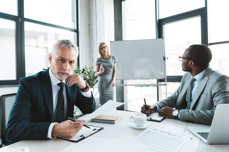 starszy biznesmen patrzeje kamerę podczas gdy mieć rozmowę z kolegami obraz stock