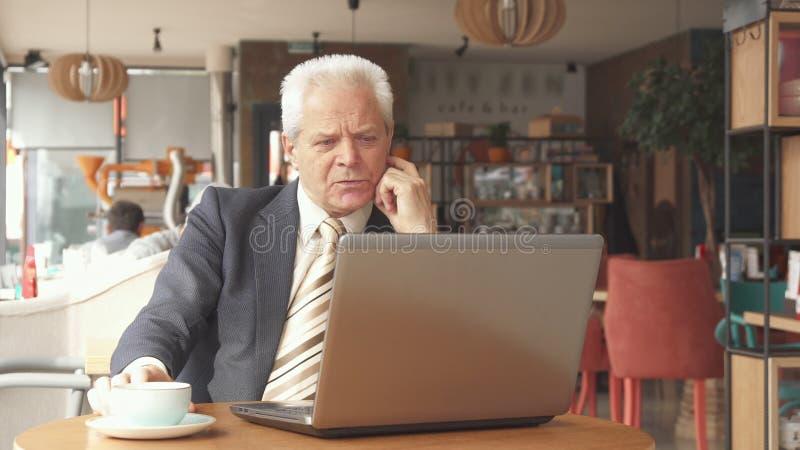 Starszy biznesmen patrzeje laptopu ekran zdjęcia royalty free
