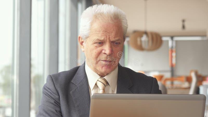 Starszy biznesmen pije gorącego napój przy kawiarnią fotografia royalty free
