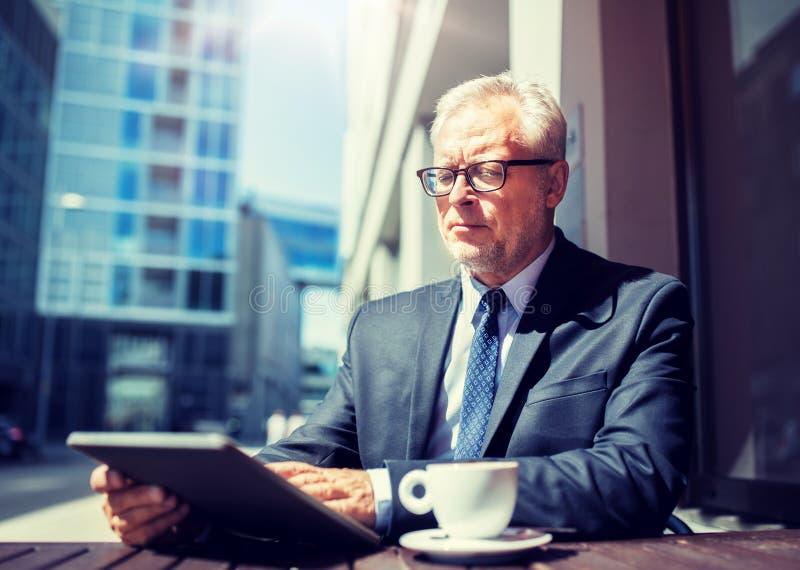 Starszy biznesmen pije kaw? z pastylka komputerem osobistym zdjęcie royalty free