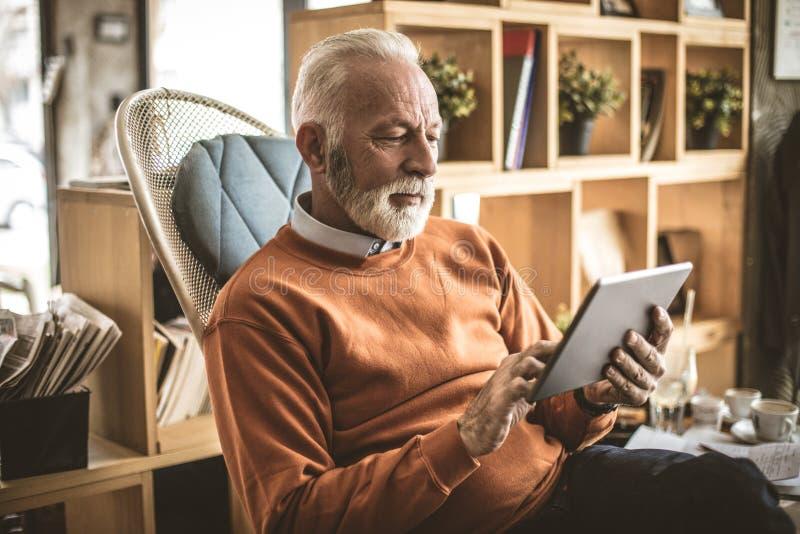 Starszy biznesmen przy jego dom używać cyfrową pastylkę obraz stock