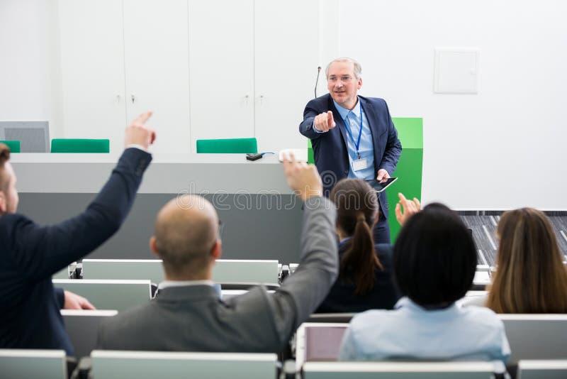 Starszy biznesmen Pyta pytania koledzy Podczas gdy Dawać P fotografia stock
