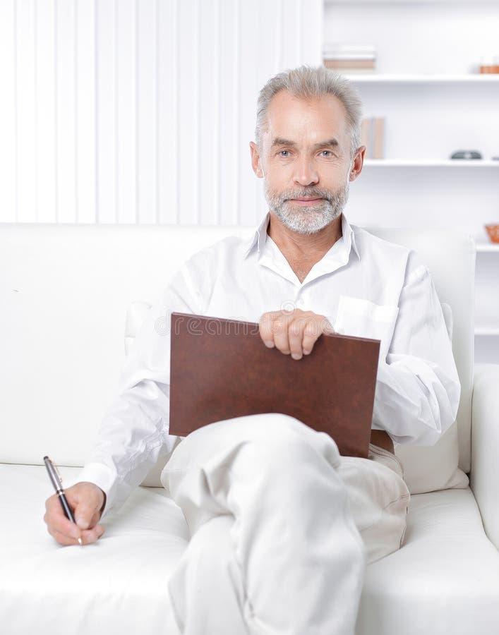 Starszy biznesmen robi notatce w workbook obraz stock