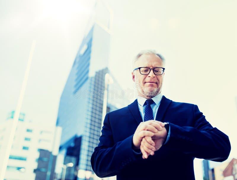Starszy biznesmen sprawdza czas na jego wristwatch fotografia royalty free