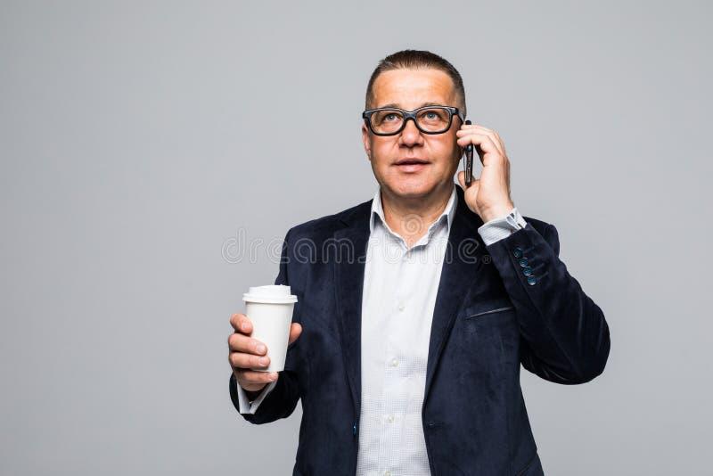 Starszy biznesmen trzyma filiżankę podczas gdy opowiadający na telefonie komórkowym odizolowywającym przeciw białemu tłu obraz stock