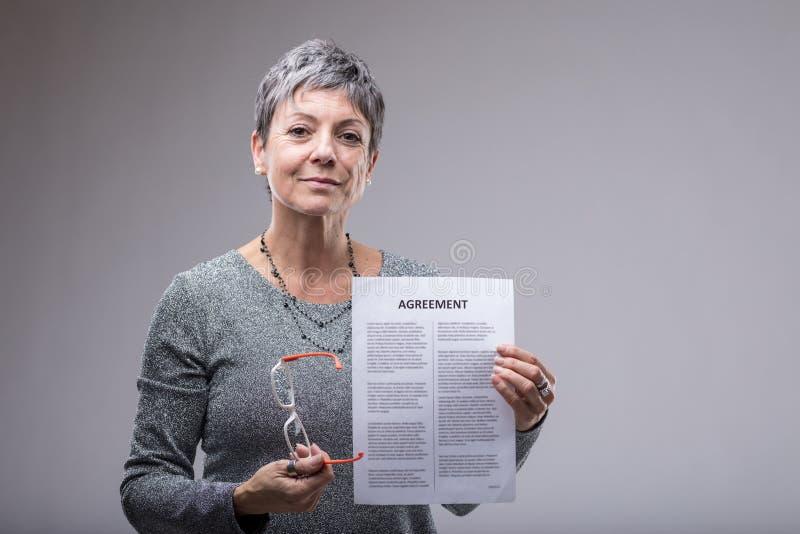 Starszy bizneswoman trzyma up pisać na maszynie zgodę zdjęcie royalty free