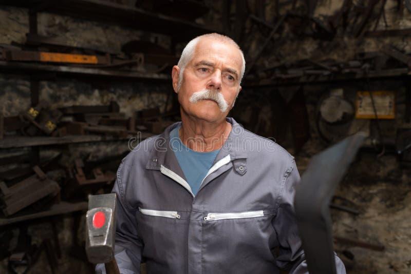 Starszy blacksmith mienia narzędzie zdjęcie royalty free