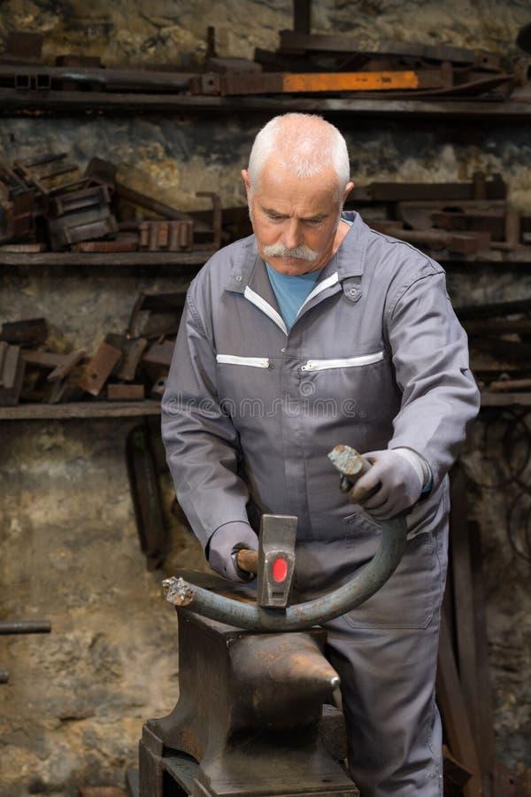 Starszy blacksmith skucia metal na kowadle zdjęcie stock