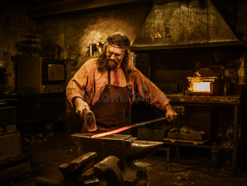 Starszy blacksmith skucie stopiony metal na kowadle w smithy fotografia stock