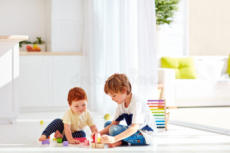 Starszy brat bawić się z małą chłopiec w kolorowych drewnianych cegłach, w domu obraz royalty free