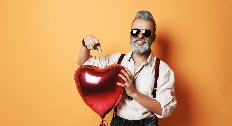 Starszy brodaty stary człowiek w lotników okularów przeciwsłonecznych chwytów serca delikatnie czerwonym balonie dla valentines d obrazy stock