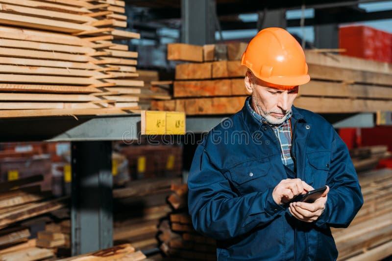 starszy budowniczy w hełmie używać smartphone outside zdjęcia stock