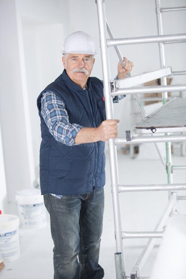 Starszy budowniczy w rusztować indoors zdjęcie stock