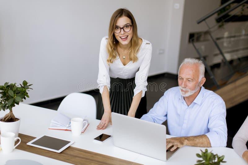 Starszy busineeman i potomstw busineswoman pracuje w biurze obrazy royalty free