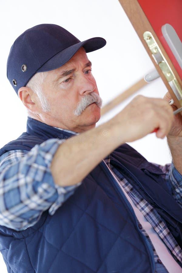 Starszy cieśli naprawiania kędziorek w drzwi z śrubokrętem zdjęcie stock