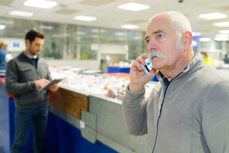 Starszy człowiek na telefonie w centrum gospodarki odpadami fotografia stock