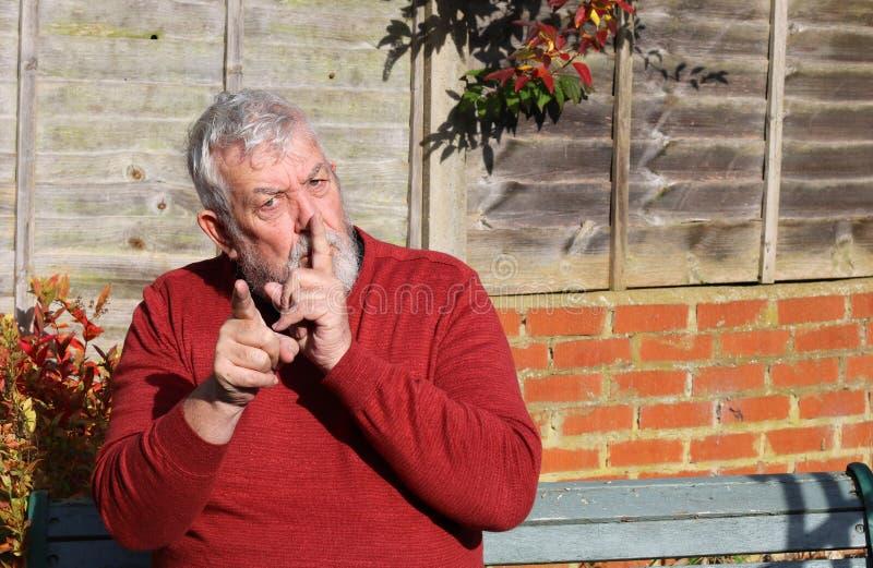 starszy człowiek Palec usta wskazywanie, był spokojny zdjęcie stock
