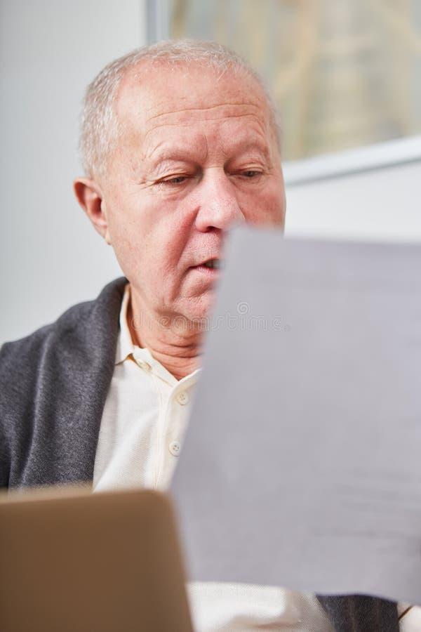 Starszy czytanie dotyczący dokument obraz stock