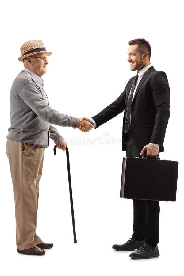 Starszy dżentelmen uściskający dłonie z młodym mężczyzną w garniturze z teczką fotografia royalty free