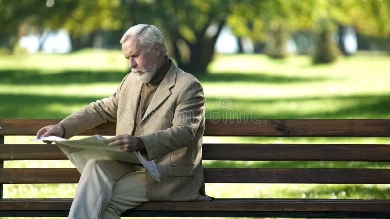 Starszy d?entelmeny czyta wiadomo??, my?le? o sytuacji politycznej, outdoors zdjęcie royalty free