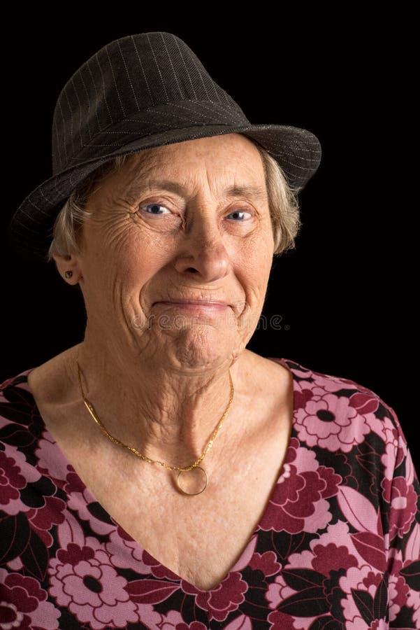 Starszy damy wearin fedora z rozbawionym spojrzeniem na jej twarzy zdjęcia royalty free