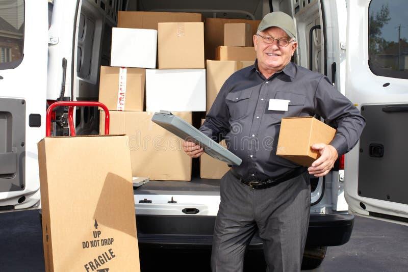 Starszy doręczeniowy mężczyzna z drobnicową pobliską ciężarówką fotografia royalty free