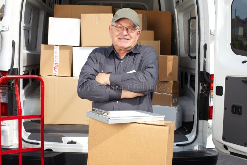 Starszy doręczeniowy mężczyzna z drobnicową pobliską ciężarówką zdjęcia royalty free
