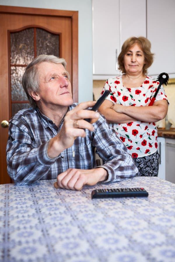 Starszy Europejski pary związek, mężczyzna ogląda tv z pilot do tv podczas gdy jego gniewna żona stoi behind w kuchni obrazy stock
