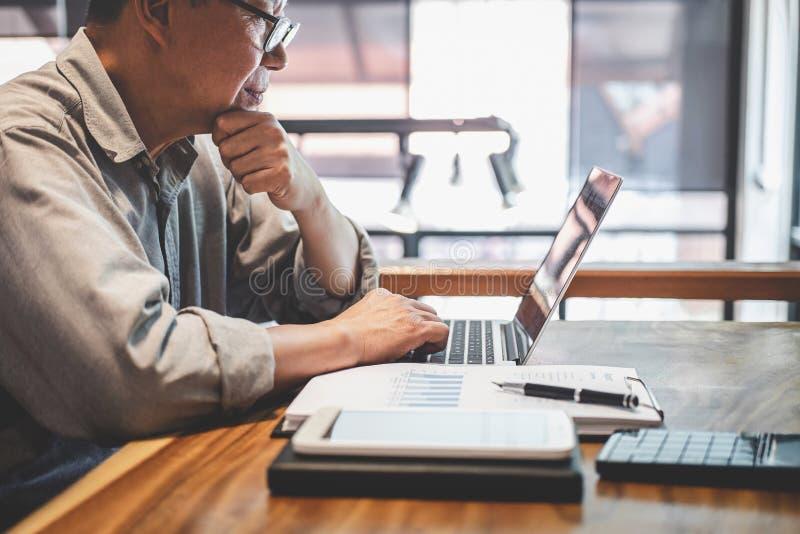 Starszy fachowy biznesmen w przypadkowej odzieży pracuje używać laptop w kawiarni z biznesowy pracujący łączyć radio przez zdjęcie stock