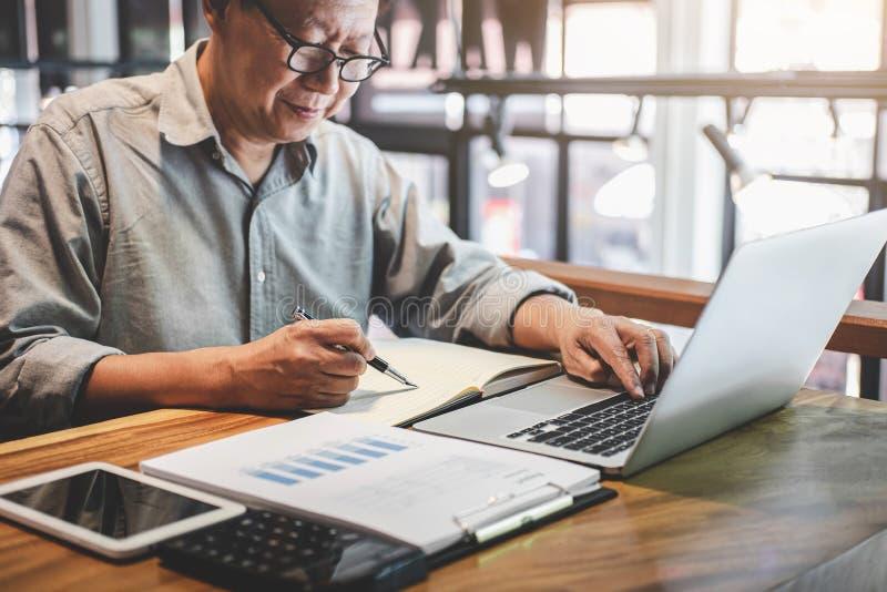Starszy fachowy biznesmen w przypadkowej odzieży pracuje używać laptop w kawiarni z biznesowy pracujący łączyć radio przez obraz stock