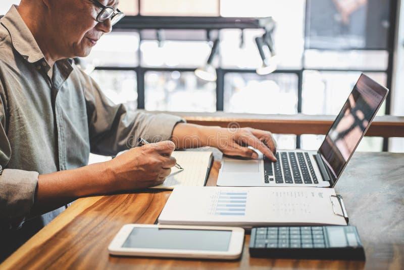 Starszy fachowy biznesmen w przypadkowej odzieży pracuje używać laptop w kawiarni z biznesowy pracujący łączyć radio przez obraz royalty free
