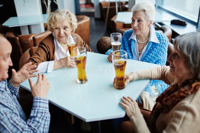 Starszy gawędziarz zabawia jego żeńskich przyjaciół obrazy royalty free