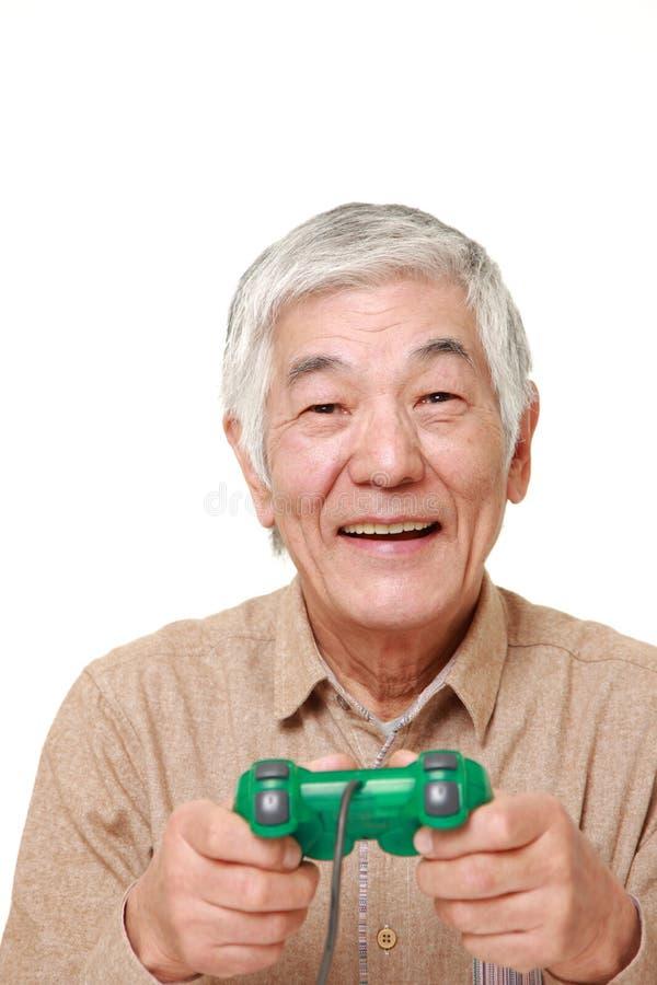 Starszy Japoński mężczyzna cieszy się wideo grę obraz royalty free