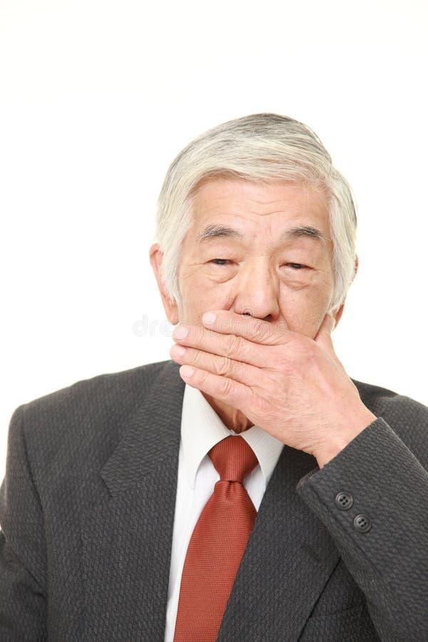 Starszy Japo?ski biznesmen robi m?wj?cemu ?adny z?emu gestowi obraz royalty free