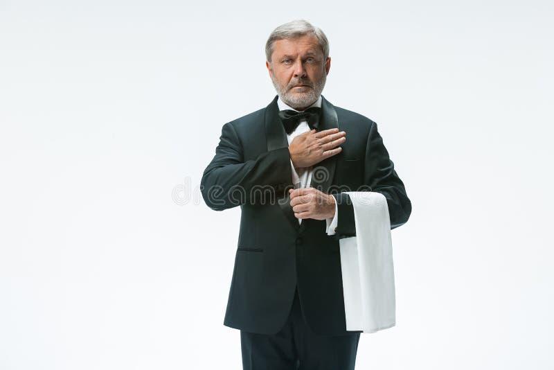 Starszy kelner z białym ręcznikiem Szyldowy język w restauraci obraz stock
