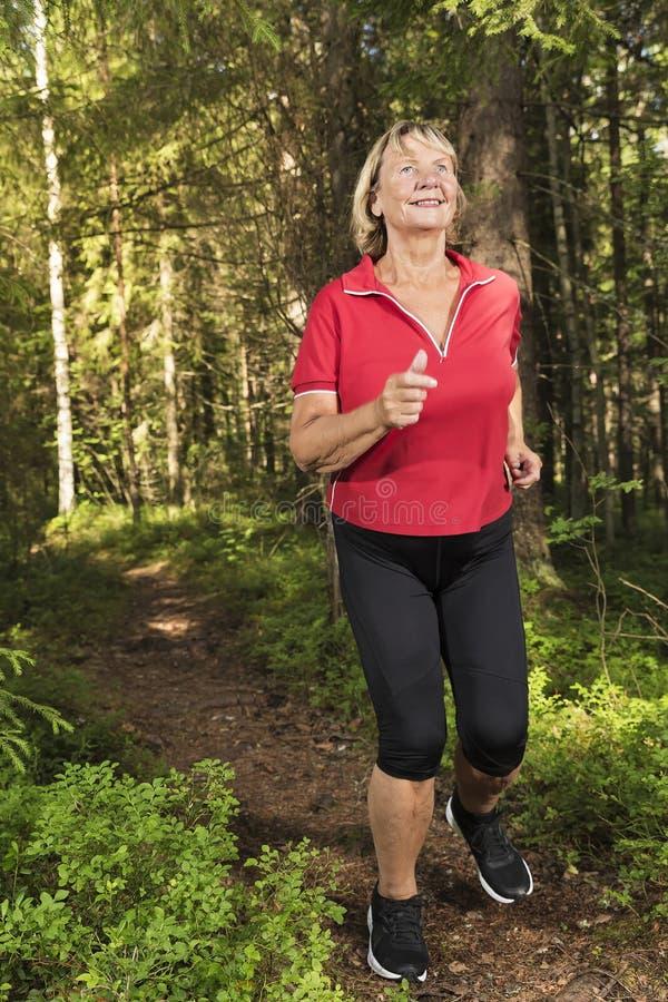 Starszy kobieta bieg przy lasem zdjęcia stock
